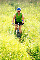 A mature woman riding a mt bike through a grassy field.