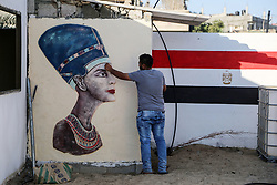 June 1, 2017 - Rafah, Gaza Strip, Palestinian Territory - A Palestinian artist paints on a mural drawings of Pharaonic figure at a technical site in the southern Gaza Strip town of Rafah, near the border with Egypt, on June 1, 2017. Young artists Palestinian artists Nidal Al-Jarami and Wissam Makkawi recreated Egypt's landmark sites with mural paintings and sculptures, including the Pyramids of Giza and a remake of an Umm Kulthum Cafe, named after the late Egyptian diva who died in 1975  (Credit Image: © Mohammed Dahman/APA Images via ZUMA Wire)