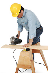 Carpenter wearing hard hat cutting a plank on a saw horse with a power saw.