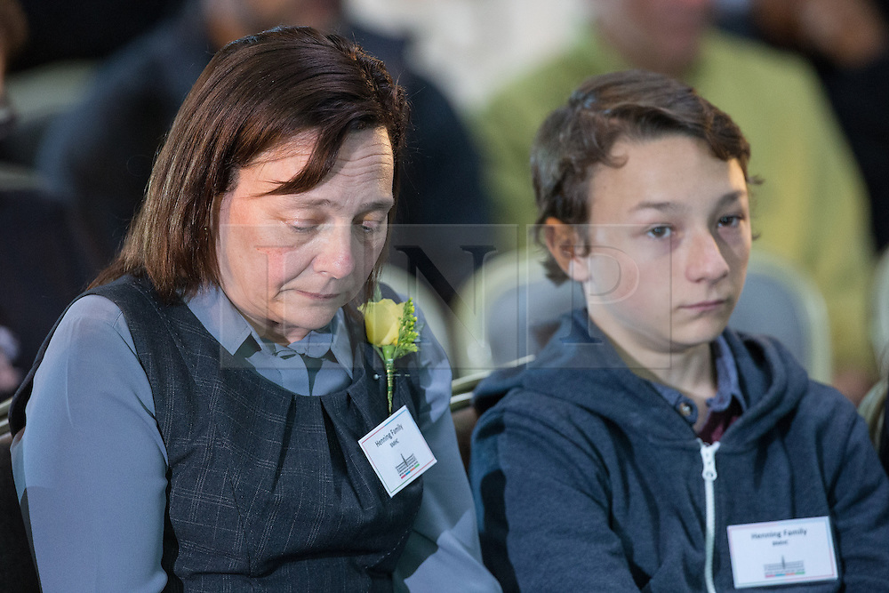 © Licensed to London News Pictures . 12/10/2014 . Manchester , UK . Members of Alan Henning's family - his wife and son - watch as a short tribute film in played at an interdenominational memorial service in memory of the murdered British aid worker , Alan Henning , hosted at the British Muslim Heritage Centre in Manchester . Photo credit : Joel Goodman/LNP