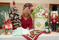 Di Greenwood goes through items including spectacular Theme Baskets Raffle items that will be available during the annual Nutcracker Christmas Fair at Sainte Andre Bassette Parish on November 7th and 8th.  (Karen Bobotas/for the Laconia Daily Sun)