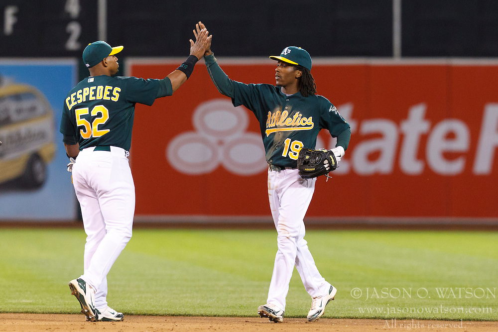 April 9, 2012; Oakland, CA, USA; Oakland Athletics second baseman Jemile Weeks (19) celebrates with center fielder Yoenis Cespedes (52) after the game against the Kansas City Royals at O.co Coliseum.  Oakland defeated Kansas City 1-0. Mandatory Credit: Jason O. Watson-US PRESSWIRE