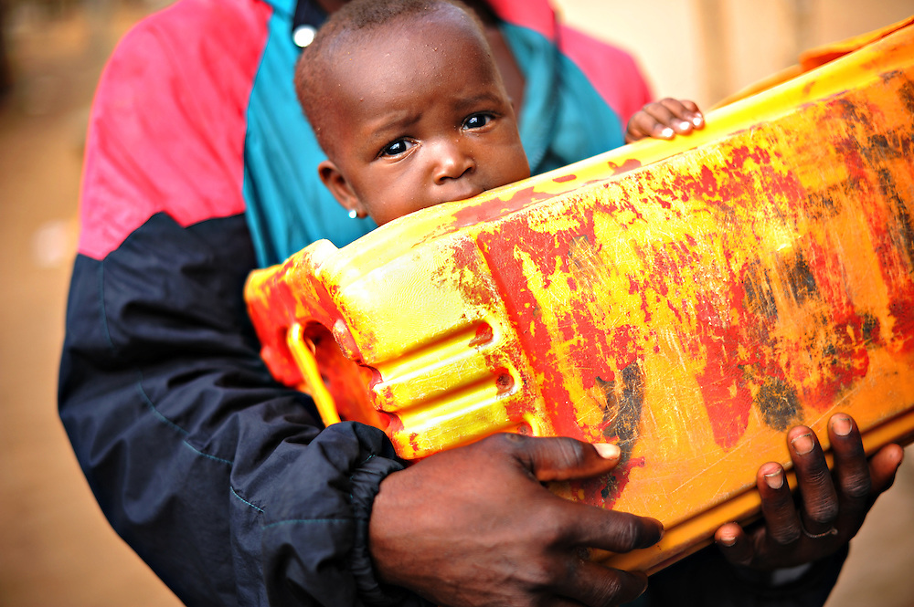 12-03-03  --  ANEHO, TOGO  --  A six-month-old baby is cradled in a hollowed out jerry can in Aneho, Togo.  The border town is frequented by fuel smugglers and many local families profit by taking part in the smuggling process. Photo by Daniel Hayduk