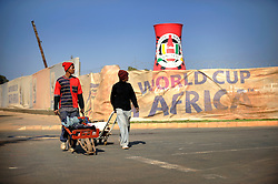 Locals walk past the construction of Soccer City, the stadium venue for the 2010 South Africa FIFA World Cup in Johannesburg