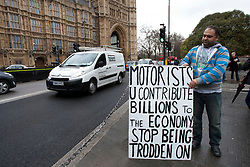 © licensed to London News Pictures. London, UK 07/03/2012. A FairFuel protester stands outside the Houses of the Parliaments with a sign as FairFuel protest group lobbying after handing in their report to Downing Street. Photo credit: Tolga Akmen/LNP