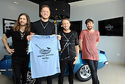 Wayne Sermon, Dan Reynolds, Ben McKee and Daniel Platzman, left to right, of Imagine Dragons, unveil Hard Rock's new Imagine Dragons Signature Series: Edition 33 T-shirt at Hard Rock Hotel Riviera Maya in Mexico, Tuesday, January 20, 2015.  A portion of the retail price from sales of the Imagine Dragons Signature Series T-shirt and pin will benefit the Tyler Robinson Foundation supporting families affected by pediatric cancer.  (Photo by Diane Bondareff/Invision for Hard Rock International/AP Images)