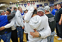 Coeur d'Alene High head football coach Shawn Amos hugs his team's running back Carlos Martinez following an assembly Wednesday at the school to celebrate the Viking's back-to-back state football championships.