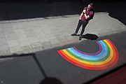 A man alongside an NHS supporting rainbow, waits for the next bus to arrive at a bus stop in Waterloo where the pavement gas been widened for socially distancing pedestrians during the Coronavirus pandemic lockdown, on 3rd July 2020, in London, England.