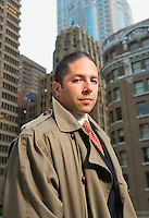 Sleepy businessman outdoors in an urban setting surrounded by big buildings..**Not released for use in legal profession**