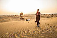 A woman on a camel trek tour in the Thar Desert of Eastern Rajasthan watching the sunset with her camels and drivers / guides. Rajasthan, India.