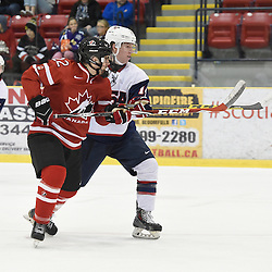 WELLINGTON, - Dec 11, 2015 -  Exhibition Game 2- Team USA vs Team Canada East at the 2015 World Junior A Challenge at the Wellington District Community Centre, ON. Sam King #22 of Team Canada East battles for control with Josh Wilkins #14 of Team United States during the second period.<br /> (Photo: Andy Corneau / OJHL Images)