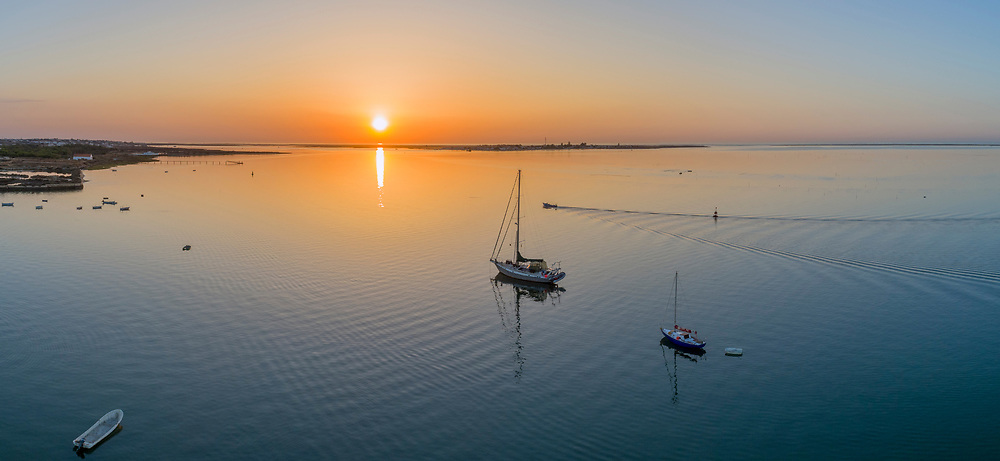 Sunrise aerial seascape view of Olhao dockyard, waterfront to Ria Formosa natural park with Armona island in background. Algarve. Portugal.
