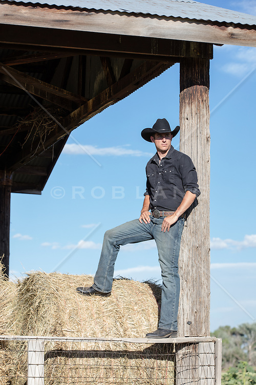 cowboy standing on a barn fence looking out