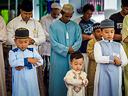25 JUNE 2017 - BANGKOK, THAILAND: Men participate in Eid al-Fitr prayers at Bang Luang Mosque. Eid al-Fitr is also called Feast of Breaking the Fast, the Sugar Feast, Bayram (Bajram), the Sweet Festival or Hari Raya Puasa and the Lesser Eid. It is an important Muslim religious holiday that marks the end of Ramadan, the Islamic holy month of fasting. Muslims are not allowed to fast on Eid. The holiday celebrates the conclusion of the 29 or 30 days of dawn-to-sunset fasting Muslims do during the month of Ramadan. Islam is the second largest religion in Thailand. Government sources say about 5% of Thais are Muslim, many in the Muslim community say the number is closer to 10%.    PHOTO BY JACK KURTZ