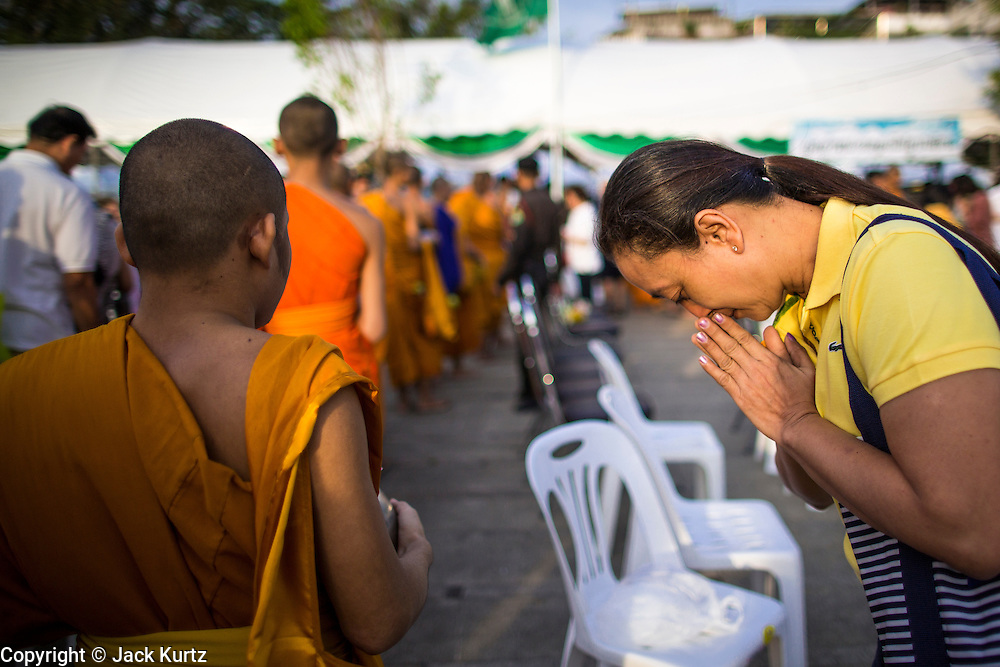 "01 JANUARY 2013 - BANGKOK, THAILAND:  A woman bows in respect after presenting a monk with an offering during a special merit making ceremony at Bangkok City Hall New Year's morning. Many Thais go to Buddhist temples and shrines to ""make merit"" for the New Year. The traditional Thai New Year is based on the lunar calender and is celebrated in April, but the Gregorian New Year is celebrated throughout the Kingdom.     PHOTO BY JACK KURTZ"