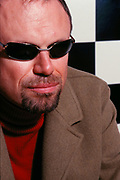 DJ Joey Negro wearing a red polo neck, brown jacket and sunglasses
