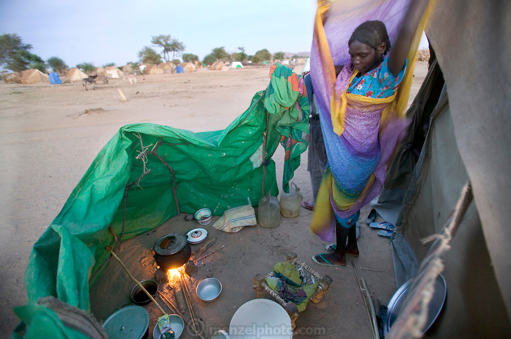 (MODEL RELEASED IMAGE). As she arranges her clothes in the chilly desert dawn, D'jimia Ishakh Souleymane, a Sudanese widow at a refugee camp in neighboring Chad, watches the pot of water she is heating to make aiysh (porridge). Anticipating the new moon at the end of the month of Ramadan, when Muslims fast, she is preparing a celebratory meal for her five children. Hungry Planet: What the World Eats (p. 21).