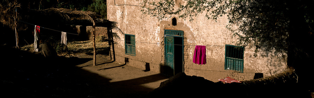 Purple clothing hanging in front of stone home