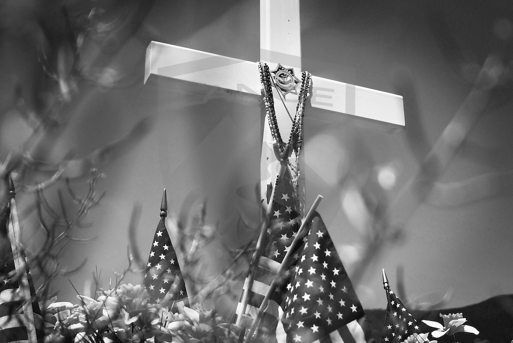 roadside cross memorial for fallen police officer jame mcgrane with american flags in black and white who was shot and killed here while on duty march 22, 2006, tijeras, new mexico