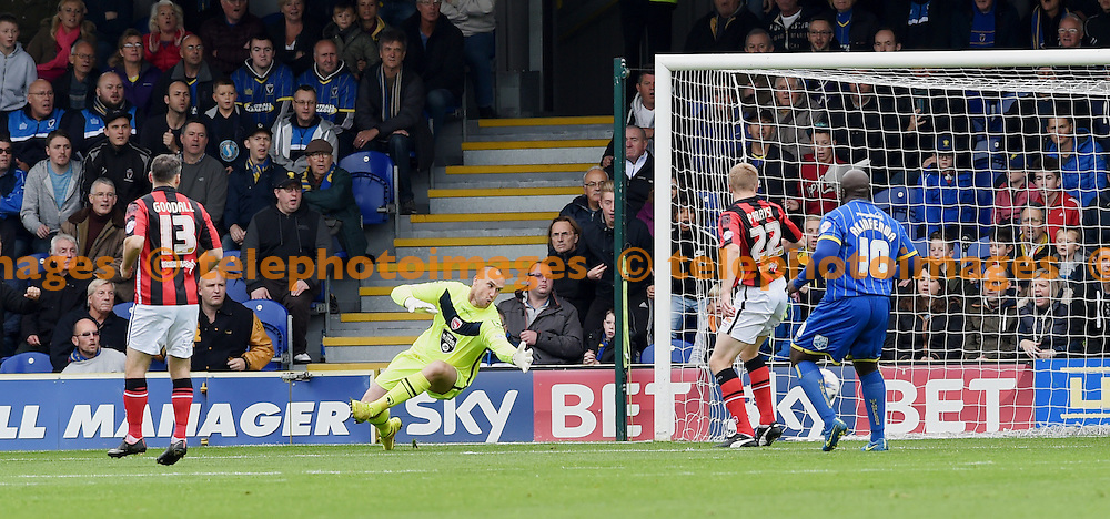 Barry Roche of Morecambe is beaten by the shot of Andy Barcham for Wimbledon's early goal during the Sky Bet League 2 match between AFC Wimbledon and Morecambe at the Cherry Red Records Stadium in Kingston. October 17, 2015.<br /> Simon  Dack / Telephoto Images<br /> +44 7967 642437