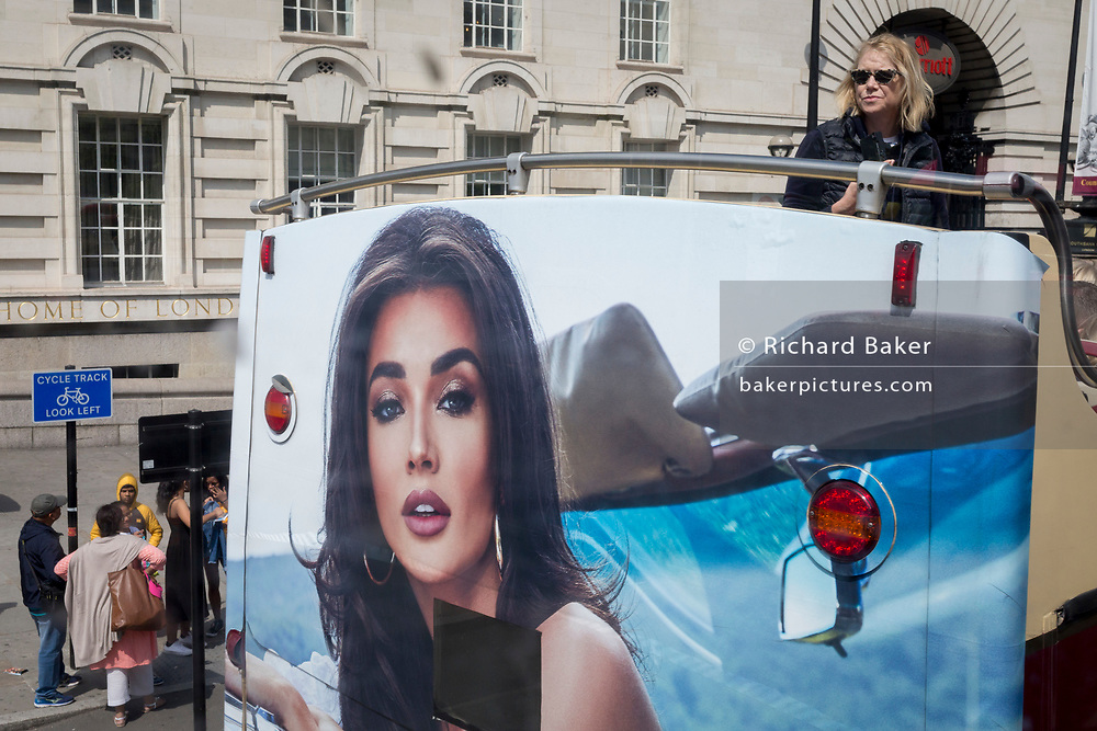 A female tourist stands up on the top deck of a London tour bus that features the face of an advertisement woman, on 11th June 2019, in London, England.
