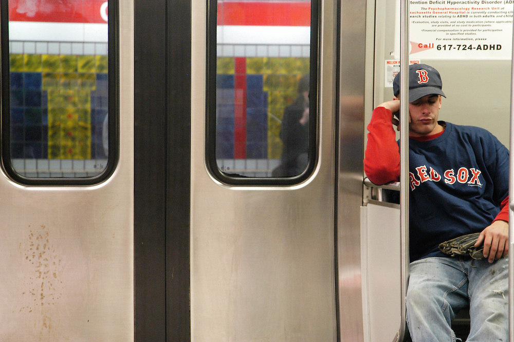 An exhausted fan rides home on the Red Line after the Red Sox beat the Yankees in the 14th inning of Game 5 in the 2004 American League Championship Series.