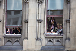 © Licensed to London News Pictures . 14/10/2016 . Manchester , UK . Crowds watch from windows of the Town Hall as the Duke and Duchess of Cambridge lay a wreath during a service at the Cenotaph at Manchester Town Hall during a dedication service , on their visit in Manchester . Photo credit : Joel Goodman/LNP