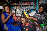A group of mothers at a hairdressing stall in Kalerwe market, Kampala, Uganda. These mothers have joined up with Miles2Smiles and enrolled their children in the day care centre. .Miles2Smiles Welfare Centre in Kalerwe market, Kampala, Uganda. The centre is a day care and welfare service for market vendors with babies and infants aged 6 months to 5 years old.