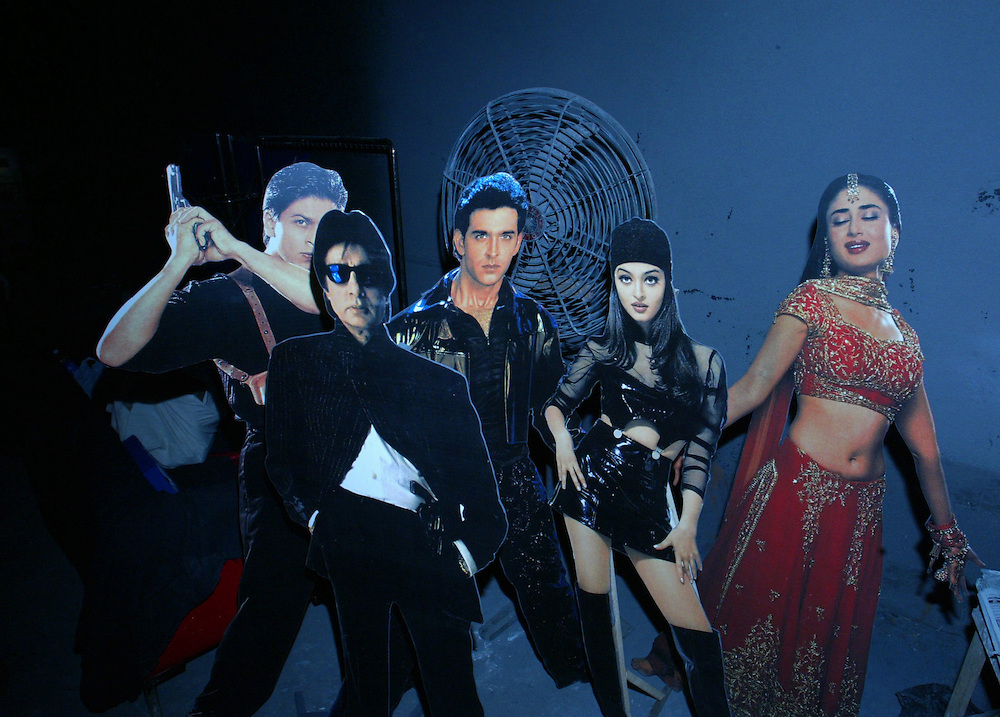 Bollywood Star cut outs, from left to right, Shahrukh Khan, Amitabh Bachan,Hrithik Roshan, Aishwarya Rai, Karina Kapoor, stand next to a fan in a film studio in Mumbai, India December 8, 2004.