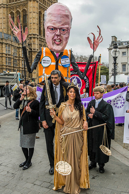 Hundreds of lawyers and barristers staged a protest at Westminster against legal aid cuts. They carried with them a huge effigy of Chris Grayling, the Justice Minister and were led by 'Justice' (pictured) in a gold costume.<br /> <br /> Speakers included - Sadiq Khan is the Labour MP for Tooting and shadow minister for London, Shami Chakrabarti Director of Liberty, Blur drummer-turned-solicitor Dave Rowntree and Paddy Hill, one of the Birmingham Six.  Houses of Parliament, Westminster, London, UK 07 March 2014.<br /> Guy Bell, 07771 786236, guy@gbphotos.com