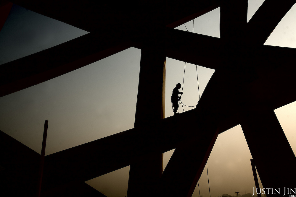"A construction worker builds the ""Bird's Nest"" National Stadium, which will be unveiled for the 2008 Summer Olympics."