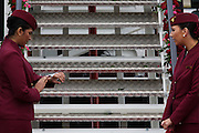 Cabin crew hostess checks her watch at the bottom of steps a Qatar Airways Boeing 787 at the Farnborough Air Show, UK.