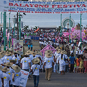 People walking to the promenade to view the floats at the end of the Balayong Festival parade. The festival at the beginning of March commemorates the founding anniversary of the City of Puerto Princesa, Palawan, highlighted by balayong tree-planting, street dancing and a colourful floral parade depicting the Palawan cherry blossoms from which the festival derives its name. The Palawan cherry is one of the most popular flowering trees in Palawan and known by the locals as the Balayong, a beautiful tree that when it is in full bloom resembles the cherry blossoms of Japan.