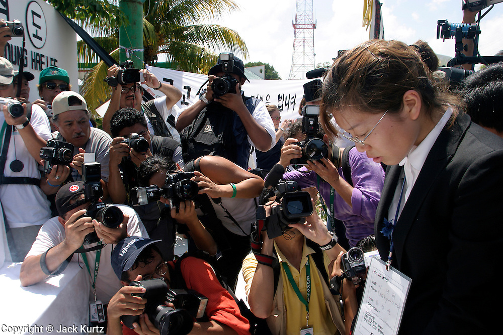 14 SEPTEMBER 2003 - CANCUN, QUINTANA ROO, MEXICO:  The daughter of Lee Kyung-hae at an alter for her father during a memorial service Sunday for her father, a Korean farm activist who publicly committed suicide Wednesday in Cancun to protest World Trade Organization agricultural policies, has been built where he died in a park in Cancun. Thousands of protestors opposed to the World Trade Organization and globalization have come to Cancun to protest the WTO meetings taking place in the hotel zone. Mexican police restricted most of the anti-globalization protestors to downtown Cancun, about five miles from the convention center.  PHOTO BY JACK KURTZ