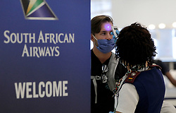 Rosemary Arends, an assistant nurse-flight attendant, checks the temperature of passengers and then helps a group of South African nationals at Miami International Airport boarding a special charter flight by South African Airways on Tuesday, April 14, 2020. Amid the coronavirus pandemic, the flight will repatriate more than 300 South African workers who were supposed to spend these months working at South Florida hotels and resorts. Photo by Pedro Portal/Miami Herald/TNS/ABACAPRESS.COM