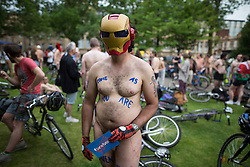 © Licensed to London News Pictures. 12/06/2015. Manchester, UK. Man wearing Ironman mask . Hundreds take part in the World Naked Bike Ride , which sees cyclists undress and cycle nude through Manchester City Centre . Photo credit: Joel Goodman/LNP