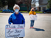 """26 APRIL 2020 - JEWELL, IOWA: LINDA BARQUIST and MARCY OLSON thank people who bought """"grab and go"""" meals during a fund raiser in Jewell. Jewell, a small community in central Iowa, became a food desert when the only grocery store in town closed in 2019. It served four communities within a 20 mile radius of Jewell. Some of the town's residents are trying to reopen the store, they are selling shares to form a co-op, and they hold regular fund raisers. Sunday, they served 550 """"grab and go"""" pork roast dinners. They charged a free will donation for the dinners. Despite the state wide restriction on large gatherings because of the COVID-19 pandemic, the event drew hundreds of people, who stayed in their cars while volunteers wearing masks collected money and brought food out to them. Organizers say they've raised about $180,000 of their $225,000 goal and they hope to open the new grocery store before summer.         PHOTO BY JACK KURTZ"""