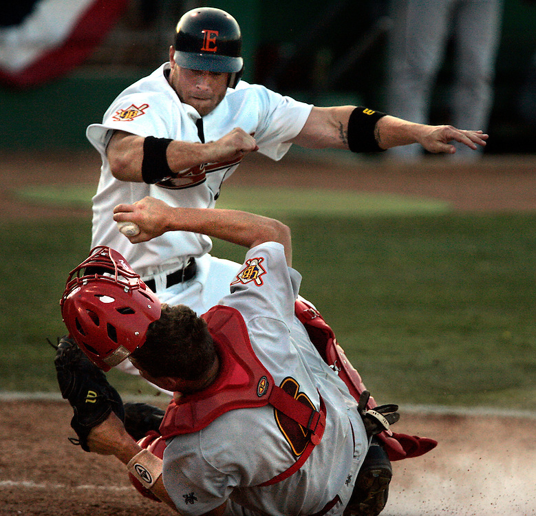 Edinburg, TX / 2006 - Edinburg Coyote baserunner Eli Albertson (#5) collides with Laredo Bronco catcher Kevin Gram (#6) on a play at the plate during the Coyotes home opener against the Broncos at Edinburg Baseball Stadium Tuesday night. Photo By Mike Roy / The Monitor