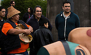 Master carver Moy Sutherland (right) standing with his father Moy Senior (middle) and Uncle Tim Sutherland (left) and First Nations people gathered at the Victoria Native Friendship Centre to celebrate the raising of a new 6000 pound totem pole in Victoria, British Columbia Canada on Thursday March 24, 2016. The pole was carved by six Aboriginal Youth working along side Moy Sutherland with the project taking over four and a half months to complete. The theme of the pole is transformation and was part of an empowerment project training youth in the art of traditional carving. (KevinLightPhoto)