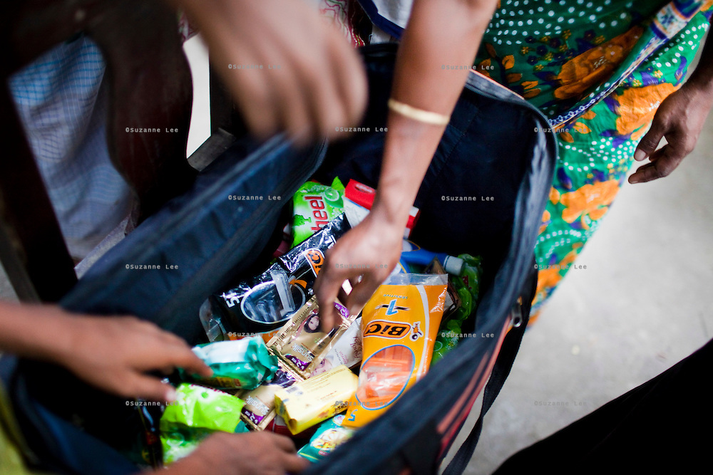 Shahida Begum, 35, looks into her product bag in her hut's compound in Palashbari Villlage, Taragonj, Rangpur, Bangladesh on 18th September 2011, after a regular day of work as a saleswoman earning 3500 - 5000 Bangladeshi Taka per month. She is one of many rural Bangladeshi women trained by NGO CARE Bangladesh as part of their project on empowering women in this traditionally patriarchal society. Named 'Aparajitas', which means 'women who never accept defeat', these women are trained to sell products in their villages and others around them from door-to-door, bringing global products from brands such as BATA, Unilever and GDFL to the most remote of villages, and bringing social and financial empowerment to themselves.  Photo by Suzanne Lee for The Guardian