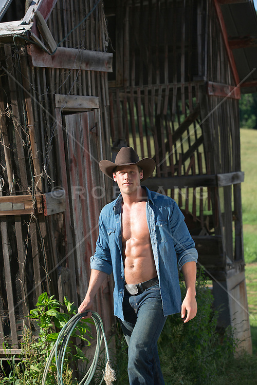 good looking cowboy with an open shirt on a ranch