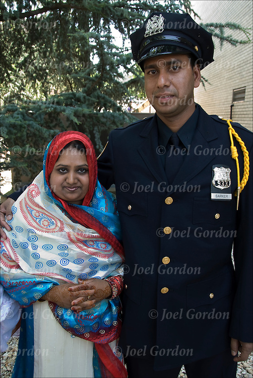Mohammad, Bangladeshi American a new NYPD police officer, the gold shoulder braid is for being in top 10% of his academic class. <br /> <br /> Posing with his arm is around wife dressed in traditional Bangladeshi clothing at the Police Academy Graduation Ceremony at St.John's University in Queens, NY.