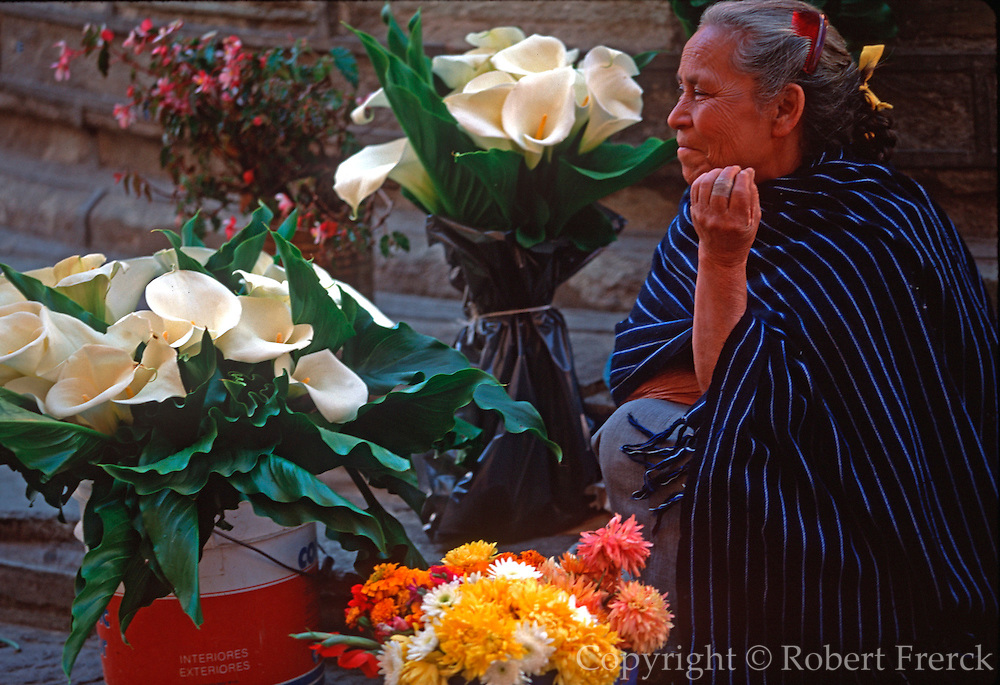 MEXICO, COLONIAL CITIES, GUANAJUATO an elderly woman selling calla lilies in the Plaza de Baratillo flower market in  the center of the city