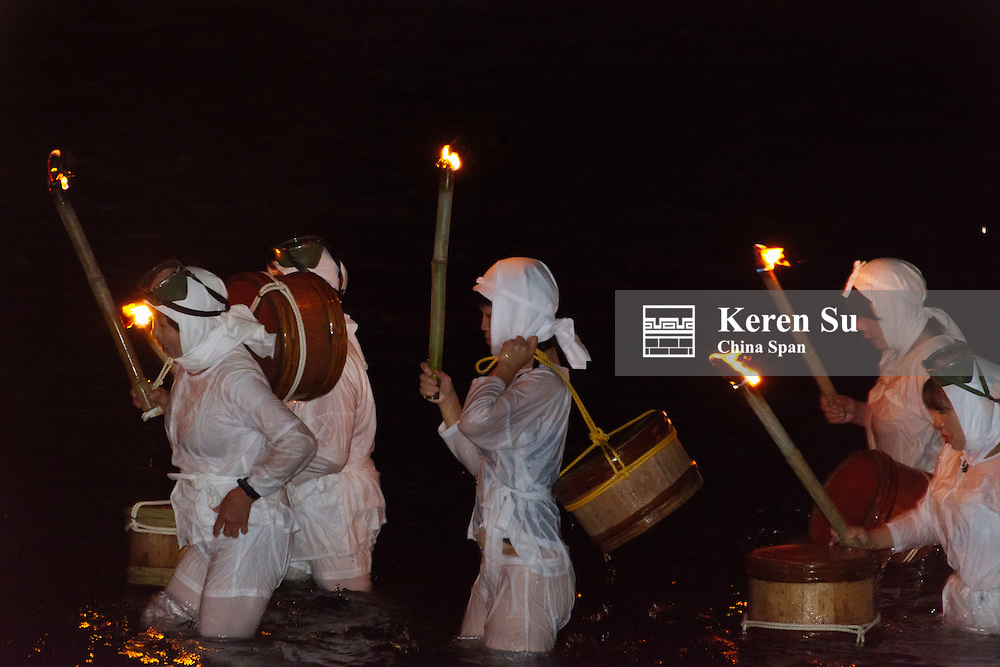 Ama women in traditional clothing swimming in the sea holding torches at night celebrating Shirahama Ama Festival, Minamiboso, Chiba Prefecture, Japan