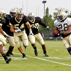July 28, 2012; Metairie, LA, USA; New Orleans Saints running back Mark Ingram (28) is chased by linebacker Will Herring (54) and cornerback Johnny Patrick (32) during a training camp practice at the team's practice facility. Mandatory Credit: Derick E. Hingle-US PRESSWIRE