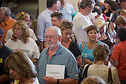 Aug 26, 2009 -- PHOENIX, AZ: A supporter of the President's health care reform waits in line to attend Sen John McCain's town hall meeting on health care at North Phoenix Baptist Church in Phoenix, AZ, Wednesday. Sen McCain hosted his second town hall meeting on health care in two days Wednesday. About 1,000 people attended the meeting. Although most were opposed to President Obama's health care proposals and supported Sen McCain, there was a large group who support the President's health care efforts.  Photo by Jack Kurtz