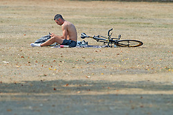©Licensed to London News Pictures 12/08/2020             Greenwich, UK. A cyclist sitting the parched grass. The hot heatwave weather continues in London and the South East today with people out and about in Greenwich park, London. Photo credit: Grant Falvey/LNP