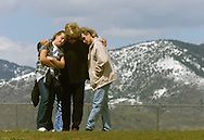 DEN101D:CRIME-SHOOTING:LITTLETON,COLORADO,27APR99 - Three generations of women mourn at the Columbine High School at 11:21 a.m. (MDT) on the one week anniversary of the shootings at the school April 27. At center is Bev Fleer hugging her daughter Cindy Sleeth (r) and granddaughter Krista Sleeth (l) all of Northglenn, Colorado.  rtw/Photo by Rick Wilking