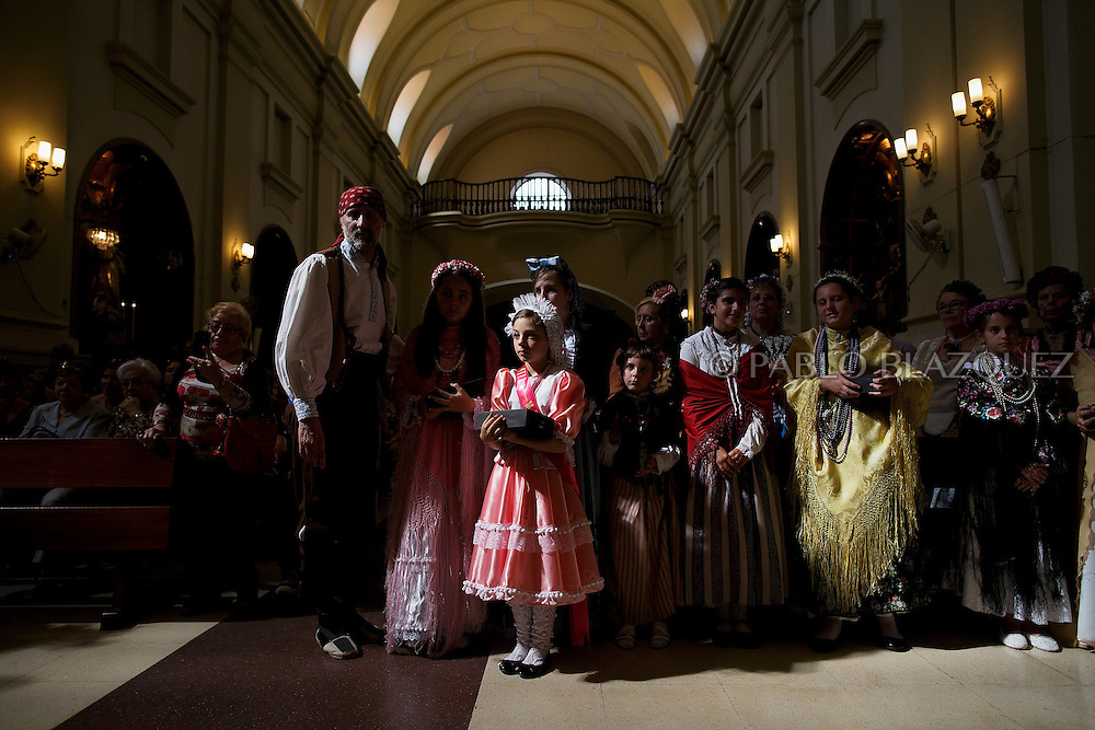'Mayas' stand inside the San Lorenzo Church amid other people as they cerebrate the 'La Maya' tradition on May 10, 2015 in Lavapies neighborhood, Madrid, Spain. 'La Maya' festivity is a pagan tradition to celebrate the beginning of the spring which is believed to come from the medieval age. In old times the 'Maya's Festival' used to take place at The 'Mayas' field' (Prado de las Mayas) which is where now the San Lorenzo church is located. La Maya combines symbols of fertility and prosperity on agriculture and shepherding economy. A 'Maya' girl dressed with traditional customs sits on an altar in the street decorated with flowers, plants and cushions. Other Mayas and Mayos offer flowers, traditional sweets, lemonade, and wine to members of the public as they play music and dance. (© Pablo Blazquez)