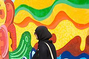 Tourists visit and take photos next to street art murals painted on the walls and architecture inside the seaside town during the International Cultural Festival, Asilah, Northern Morocco, 2015-08-10.<br /><br />Asilah is a sleepy fishing town in the North of Morocco, just one hour south of Tangier. While not completely off Morocco's well-beaten path, it's often missed by travellers bound inland for Fez or Chefchaouen, yet has a uniquely alluring charm. With an immaculately restored medina that's re-painted vivid shades of blue & white each summer, Asilah has the feel of being Morocco's own Santorini - a great spot to see the more chilled out, seaside town life in Morocco.  <br /><br />Asilah is synonymous with art and the peaceful seaside town is home to over 50 resident artists. It is packed full of art galleries, studios and exhibition spaces with artists from around the country selling their work. Each summer, the town invites artists from across the globe to visit and take part in an annual arts festival. The festival begins in July and commences by the artists and locals re-painting the medina. They purposefully leave large spaces of the medina walls white-washed blank, ready for artists to create and design new murals and street art during the festival. Artwork can be found everywhere, including sketches and engravings etched onto doorways and walls by children. Large sections are even allocated for children to paint their own ideas and fun workshops are held encouraging children to work together and help paint new murals onto the walls. This is actually how Asilah began its synonymous relationship with art. In 1978 seven Moroccan artists were invited to the town to hold art classes for children, inviting them to draw on the walls of the medina. The festival goes on for a number of weeks showcasing a range of artistic disciplines, from music and poetry to performance and painting, and everything inbetween. Its mark is left on the town for the remainder of the